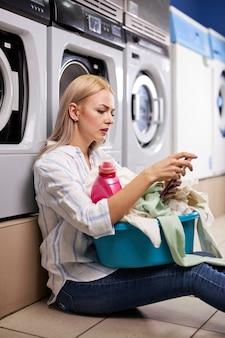 Mujer sentada en el suelo y apoyarse en una lavadora sosteniendo un teléfono inteligente en un lavadero en la casa de lavado. señora caucásica rubia esperando.