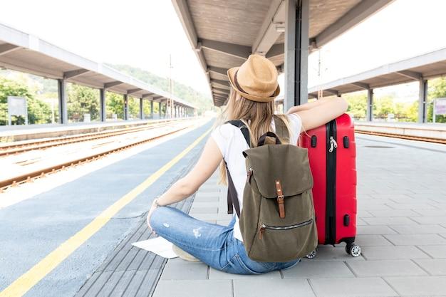 Mujer sentada en el suelo en la estación de tren