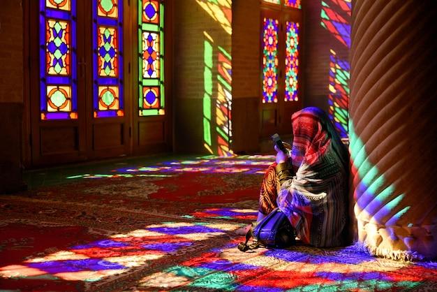 Mujer sentada en el suelo en la famosa mezquita arco iris de nasir-ol-molk en la ciudad iraní de shiraz