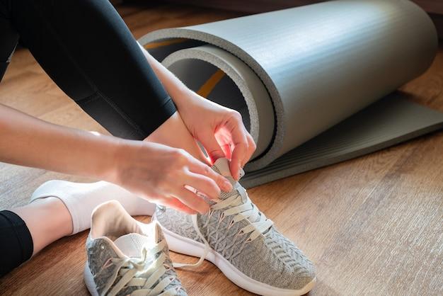 Mujer sentada en el suelo junto a la alfombra retorcida y atar sus zapatillas de deporte preparándose para la clase de yoga