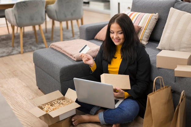 Mujer sentada en el suelo mientras realiza una nueva compra