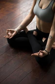 Mujer sentada en el suelo en pose de padmasana, haciendo gesto mudra