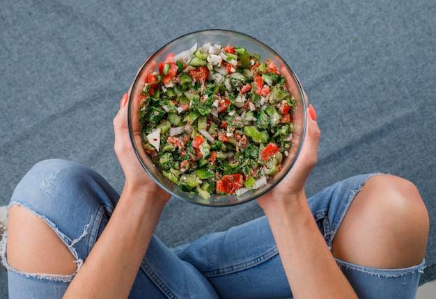 Mujer sentada en el suelo y sosteniendo ensalada de verduras en un recipiente de vidrio vista superior sobre una superficie gris