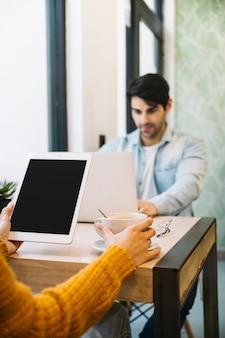 Mujer sentada con tableta y café