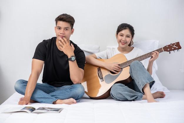 Una mujer sentada toca la guitarra y un hombre sosteniendo un libro y cantando.