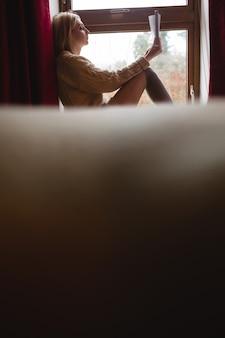 Mujer sentada en la ventana y leyendo un libro