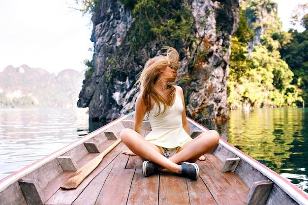 Mujer sentada en el viejo extremo del barco tradicional de tailandia explorar el parque nacional khao sok