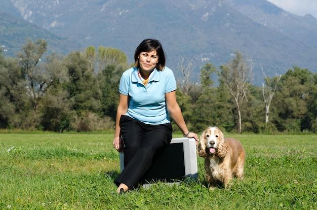 Mujer sentada en un viejo televisor en el campo con un cocker spaniel en el lateral