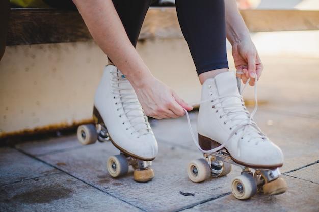Mujer, sentado, lacing, roller, patines
