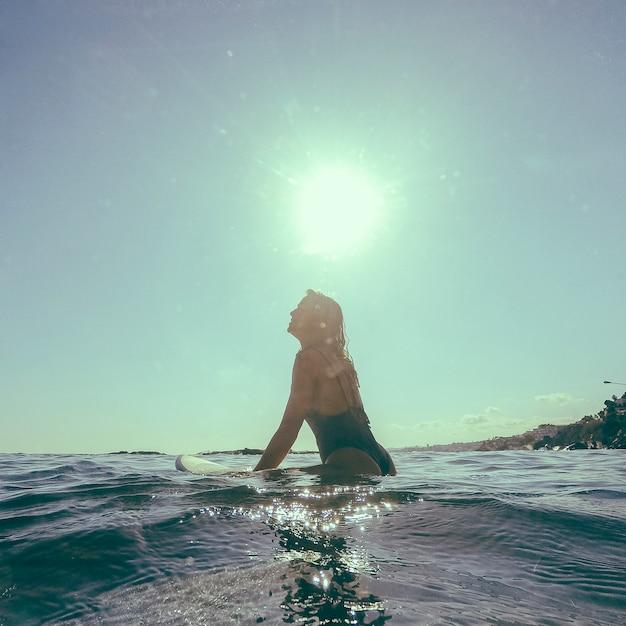 Mujer, sentado, en, tabla de surf, en, agua