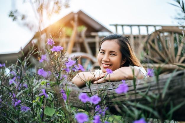La mujer se sentó feliz en el jardín de flores y puso sus manos hacia la valla de madera