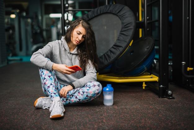 Mujer seria atlética con el teléfono inteligente sentado cerca de la botella en el gimnasio