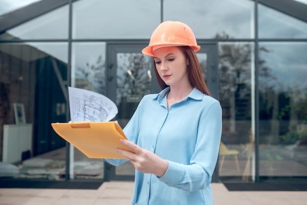 Mujer seria considerando el plan de construcción al aire libre