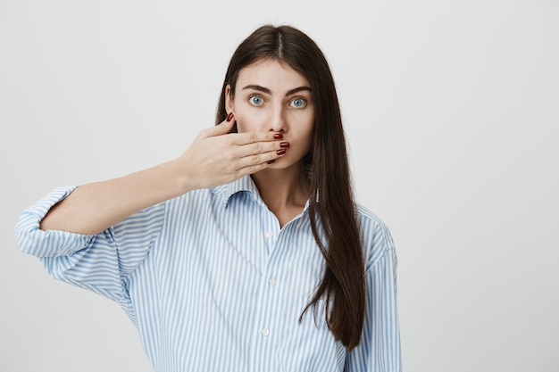 Mujer seria cubre la boca, guarda silencio