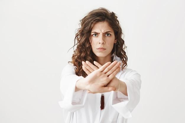 Mujer seria y decidida mostrar gesto de parada, prohibir la acción