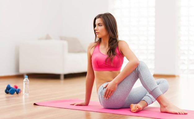 Mujer seria haciendo ejercicio de relajación en casa