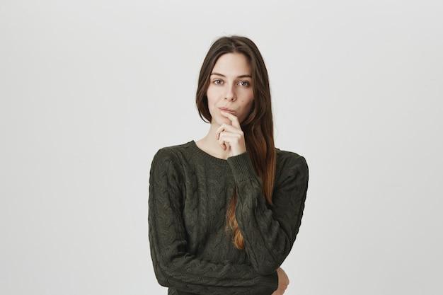 Mujer seria inteligente y creativa que piensa, toma la decisión