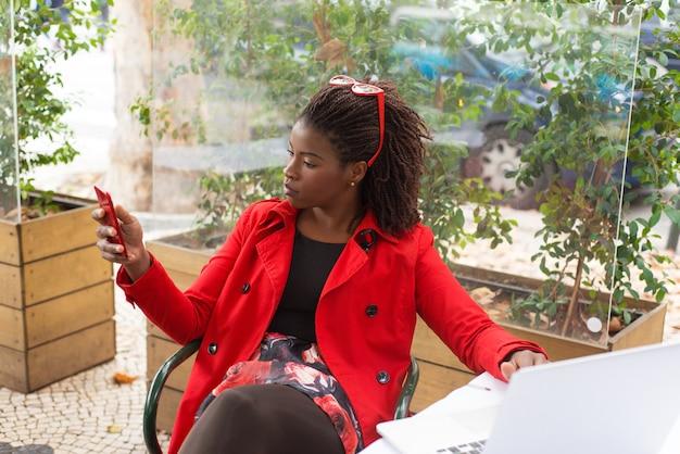 Mujer seria con laptop y smartphone en restaurante