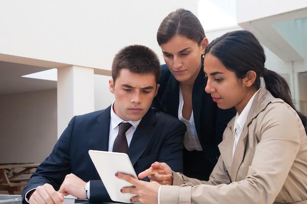 Mujer seria mostrando pantalla de tablet a gente de negocios