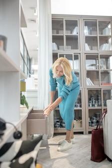 Mujer seria de pie, inclinada cerca de un pequeño armario beige, pasando las manos por la superficie del cajón, interesada.