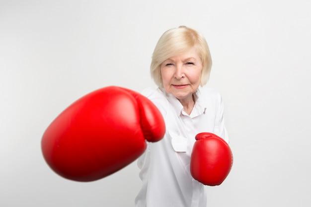 Mujer seria está de pie en posición, con guantes de boxeo rojos. ella está lista para hacer algunos ejercicios.
