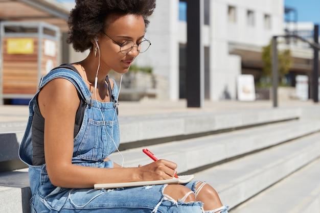 Mujer seria con piel oscura y saludable, concentrada en escribir un ensayo, sostiene la pluma, toma notas en el bloc de notas, usa ropa de mezclilla, posa en las escaleras, escucha audiolibros en auriculares, posa en la vista de la ciudad