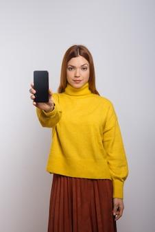 Mujer seria que sostiene el teléfono inteligente con pantalla en blanco