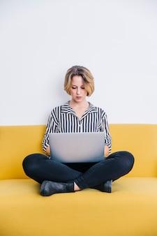 Mujer seria que usa la computadora portátil en el sofá