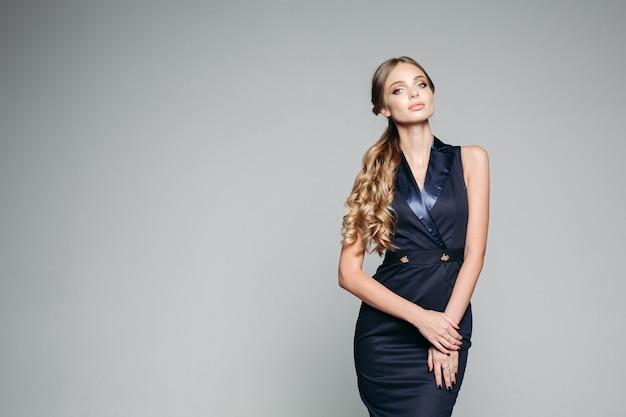 Mujer seria y seductora con elegante vestido azul oscuro.