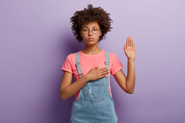 Mujer seria segura con cabello rizado hace promesa o juramento sincero, mantiene una mano en el corazón