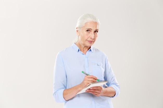Mujer seria segura escribiendo en cuaderno aislado