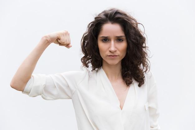 Mujer seria segura flexionando bíceps