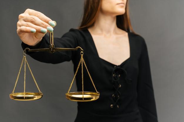 Mujer seria sosteniendo la balanza de la justicia