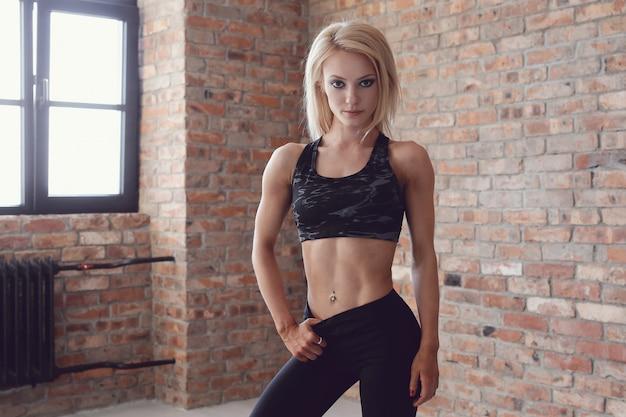 Mujer sexy atleta musculoso posando