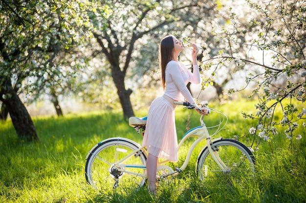 Mujer sexy con una bicicleta en un jardín de primavera