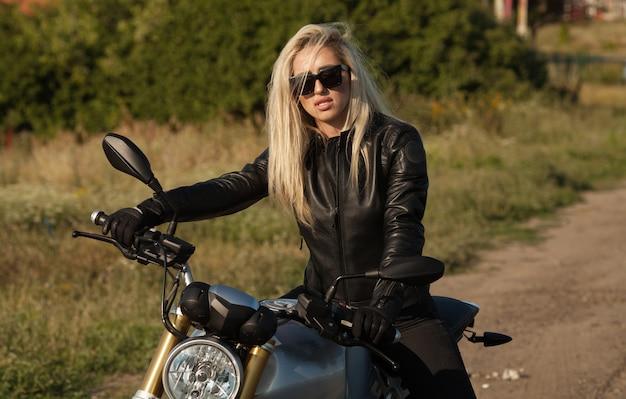 Mujer sexy biker sentado en motocicleta moderna. retrato de estilo de vida al aire libre