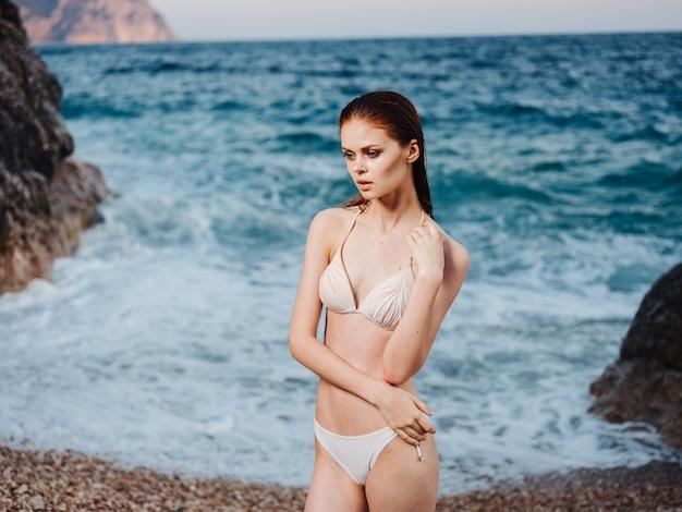 Mujer sexy en bikini modelo traje de baño pelo mojado transparente océano agua espuma blanca. foto de alta calidad