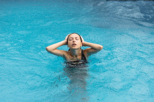 Mujer sexy blackhair mojada en traje de baño posando en la piscina