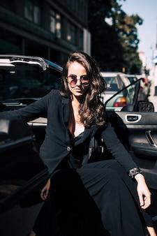 Mujer sexy de cabello castaño en el asiento del auto