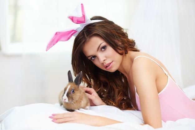 Mujer sexy con conejo marrón en la cama
