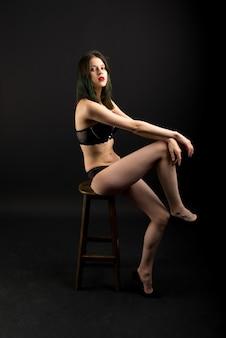 Mujer sexy, hermosa y atractiva con cuerpo delgado hermoso con ropa interior de encaje está posando en el estudio oscuro.