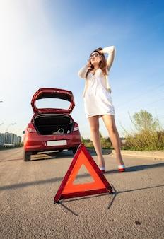 Mujer sexy llamando al mecánico después de la avería del coche