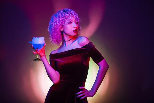 Mujer sexy y misteriosa bebiendo una bebida alcohólica azul aislada