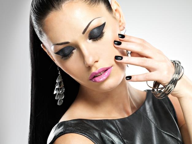Mujer sexy de moda hermosa con uñas negras en cara bonita. modelo de niña bonita con bisutería elegante de color plata.