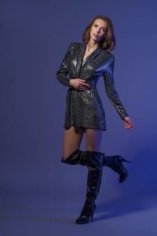 Mujer sexy de moda en vestido brillante y tacones altos