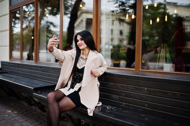 Mujer sexy de pelo negro en gafas y abrigo sentado en el banco con teléfono móvil a mano y haciendo selfie.