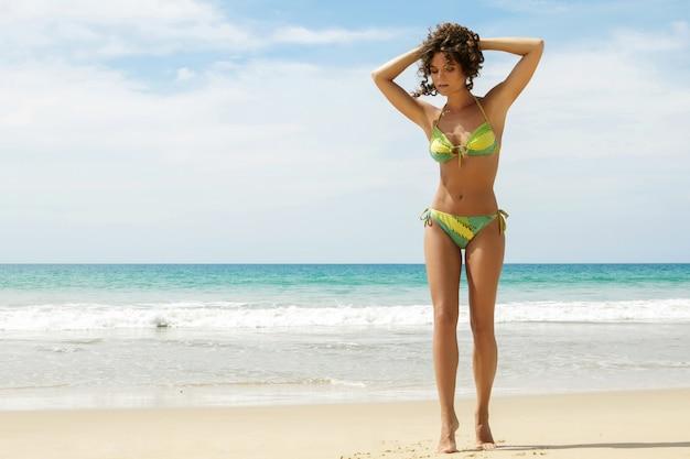Mujer sexy con el pelo rizado en la playa