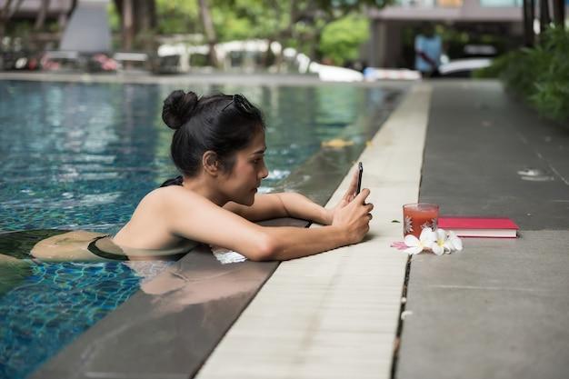 Mujer sexy en piscina jugar smartphone