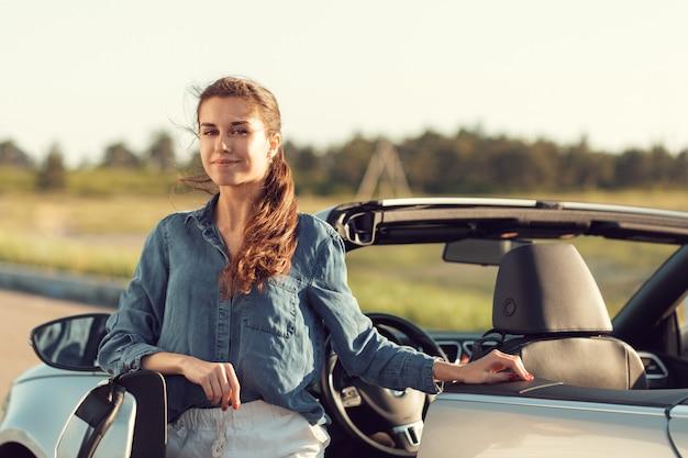 Mujer sexy posando junto al auto descapotable