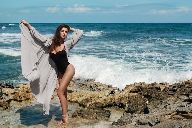 Mujer sexy en la roca junto a un mar